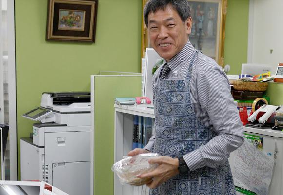 エプロンをして調理の準備をする白澤さん。